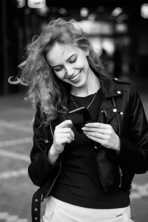 happy cute blond woman in leather coat stand on street with smartphone smiling, monochrome