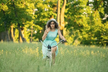 pretty woman biker on bicycle riding on green grass at sunset time