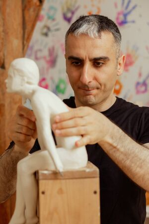 sculptor making the girl's figurine of white clay