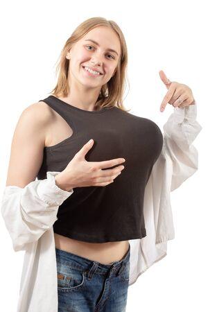 Mujer joven muestra su gran falso aislado sobre fondo blanco mirando a la cámara sonriendo