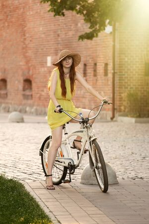 young red hair woman in hat move on bike on street