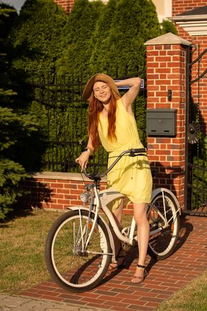 young red hair woman in hat with bike on street Stock fotó