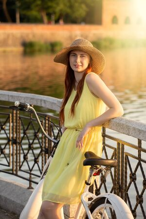 young red hair woman in hat standing with bike at sunset park Stockfoto