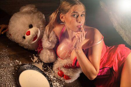 meisje in lingerie liggend op de vloer met kom melk en spatten Stockfoto