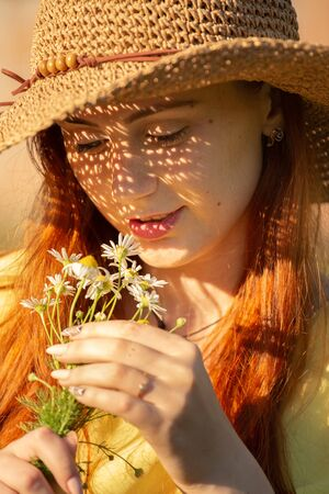 pretty red hair girl in sun hat with camomile bouquet looking on flowers, smiling, toned image