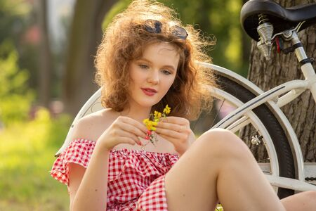 beautiful pinup girl with bare shoulders dress and curly red hair sitting with bike and flowers in sunny park in sun light 写真素材
