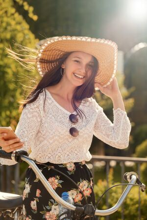 happy beautiful girl with sunhat and bike looking at camera in sun rays