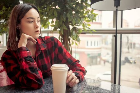 sad pensive young woman sitting in cafe, looking at window