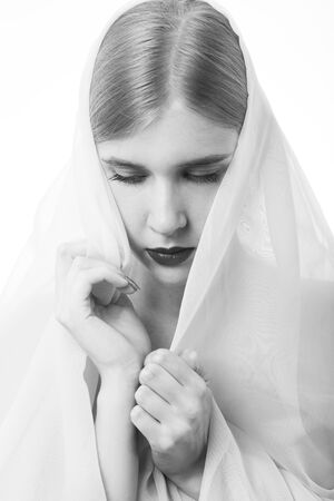 sad blond young woman with white veil on white background, monochrome Stock Photo