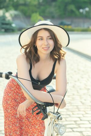 young curly hair woman in hat and dress posing with bike at old european city, sunset time, looking aside, smiling Stock fotó