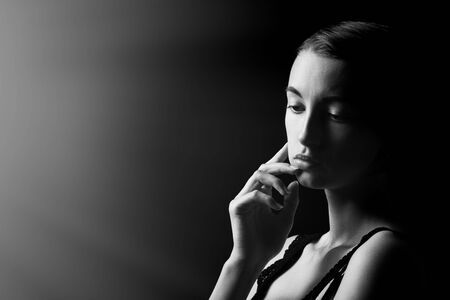 beautiful sad pensive sensual young woman on black background with copy space looking down, monochrome