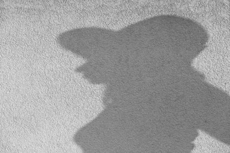 female silhouette with hat profile view at yellow concrete wall, monochrome