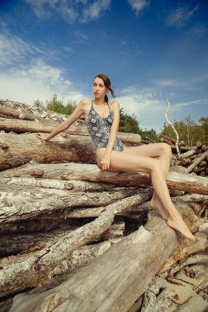 young slim woman in sneak swimwear sitting on dry logs sunbathes, looking aside, side view