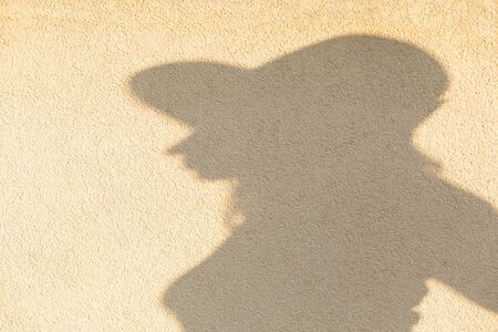 female silhouette with hat profile view at yellow concrete wall