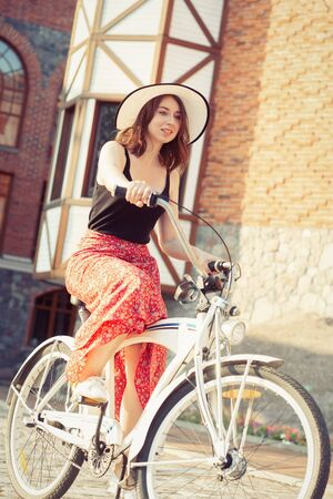 young curly hair woman in hat and dress moves on bike at old european city, sunset time, smiling Stock fotó