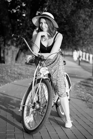 cute young woman cyclist standing looking at camera, smiling, monochrome Reklamní fotografie