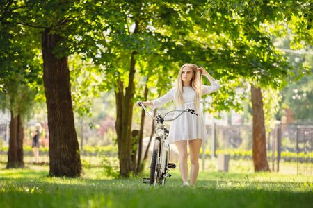 pretty blond girl in white dress with bike on green sunny park walks looks at camera Фото со стока