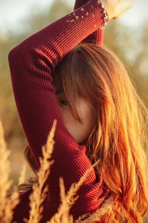 woman with long hairs cover her face in dry grass side view closeup Stock fotó