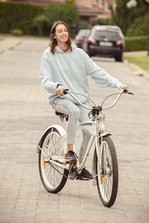 young woman cyclist moves on bicycle on road smiling, feet up