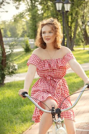 beautiful pinup girl with bare shoulders dress and curly red hair moves on bike in sunny park in sun light, looking aside