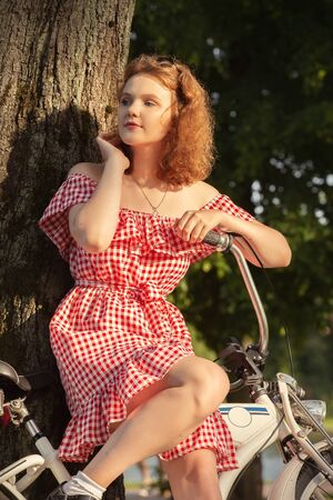beautiful pinup girl with bare shoulders dress and curly red hair standing with bike in sunny park in sun light, looking aside Stockfoto