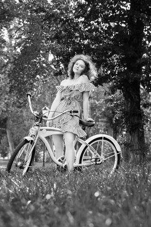 beautiful pinup girl with bare shoulders dress and curly red hair standing with bike in sunny park in sun light, looking at camera, monochrome