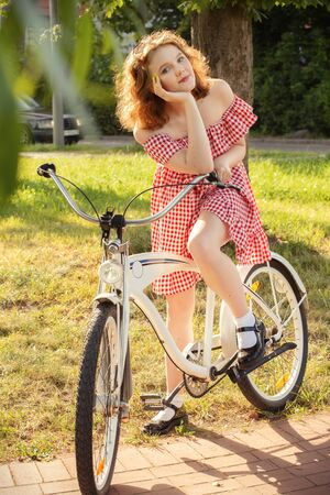 beautiful pinup girl with bare shoulders dress and curly red hair standing with bike in sunny park in sun light, looking at camera