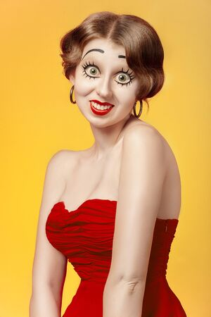 fun young woman with vintage pinup makeup making dolly face looking at camera, yellow background