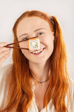 fun girl with sushi roll on white background smiling looking at camera show nose