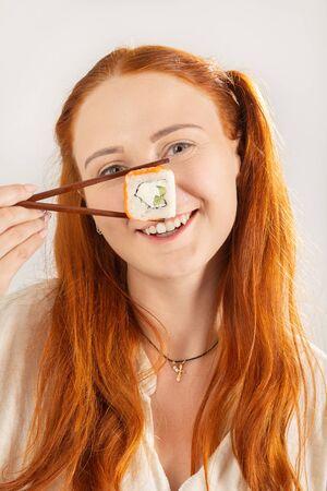 Lustiges Mädchen mit Sushi-Rolle auf weißem Hintergrund, das in die Kamera lächelt, zeigen Nase show