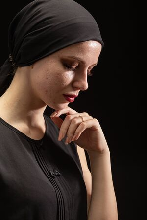 young sad woman with pimply skin on black background looking down, side view