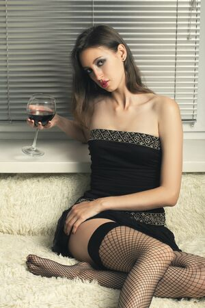 sensual young woman with wineglass sitting on bed looking at camera show her hip in stockings Фото со стока - 130048393