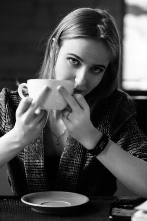 young woman in cafe with a cup shows fuck gesture looks in the camera, monochrome 免版税图像