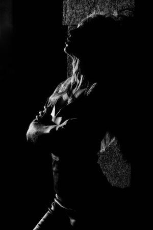 Mujer joven de pie junto a la pared, se abrazó a sí misma con los ojos cerrados, fondo oscuro con luz de fondo, monocromo