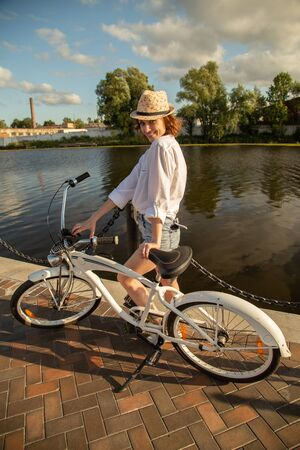 happy woman with bike posing on promenade near river, smiling