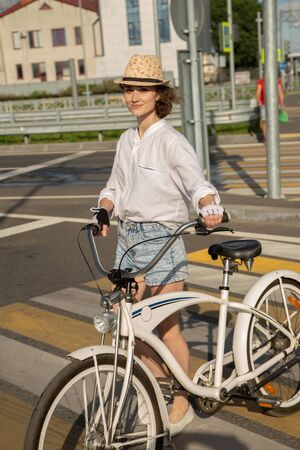 happy young woman walks on crosswalk in european city smiling