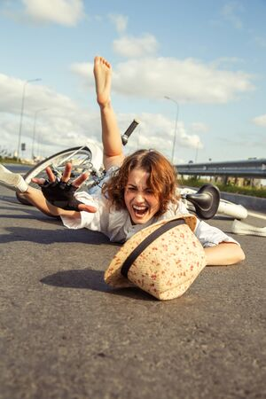 girl fell from the bicycle, lies on asphalt shouts