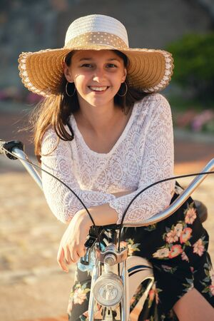 serious beautiful girl in sunhat and bike looking at camera in sun rays, smiling Stock Photo
