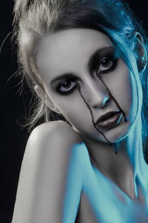 young woman with bare shoulders and Halloween bloody makeup looking at camera. studio shot. moonlight Stok Fotoğraf - 131356905