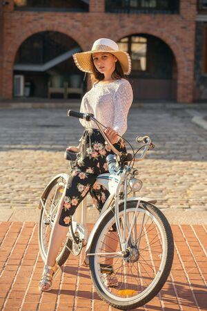 serious beautiful girl in sunhat and bike looking at camera in sun rays