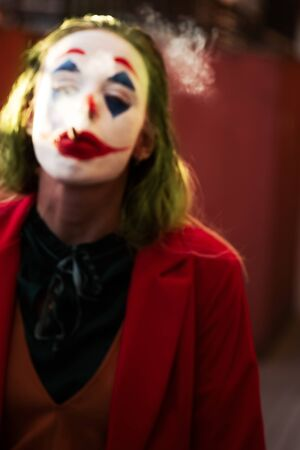 young woman with Joker makeup and costume, walks smoking. defocused blurred image