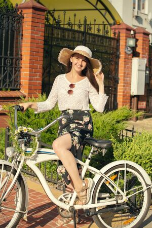 happy beautiful girl on bike looking at camera in city under sun rays