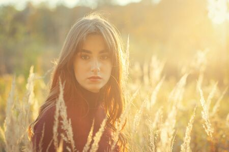 sad serious young woman in dry autumn grass looking at camera