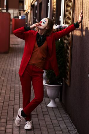 young woman with Joker makeup and costume, stand smoking