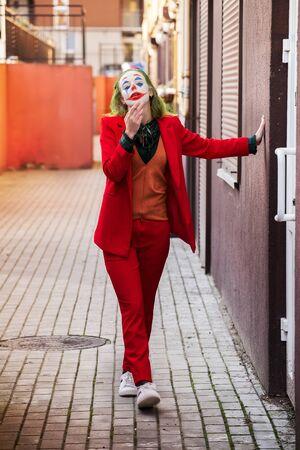 young woman with Joker makeup and costume, walks smoking