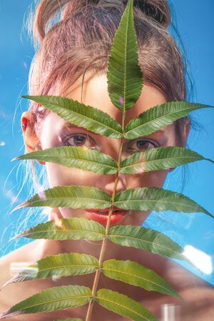 serious young woman cover her face with tropical leaf looking at camera blue background