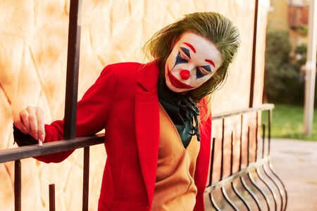 young woman with Joker makeup and costume looking down, smoking