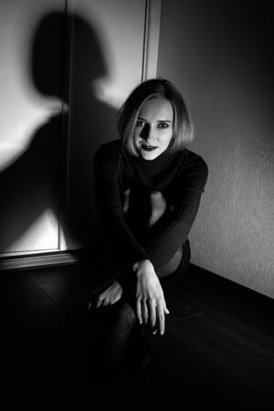 sensual beautiful young woman in black dress and tights sitting on wooden floor in dark room, monochrome