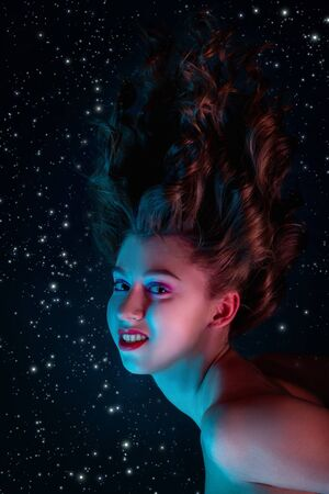 witch flying in moonlight on stars background, looking at camera smiling Stock Photo