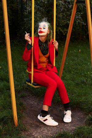Mujer joven con disfraz y maquillaje de payaso malvado, stand fumando